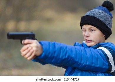 boy playing with a toy gun on the street in autumn.
