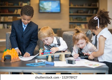 A boy playing with a toy train, others play with stationery in the business center