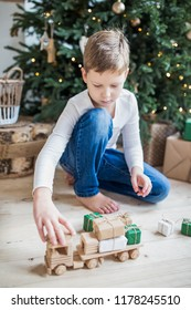 Boy playing toys under christmas tree. Wooden car with small gifts.