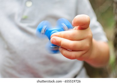 Boy playing with a Tri Fidget Hand Spinner