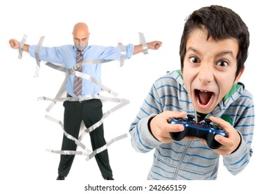 Boy playing video games and dad glued to the wall with duct tape in the background