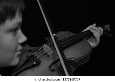 boy playing the violin in black and white