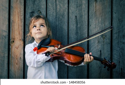 boy playing violin, happy and smiling, success and happiness, a wooden background behind him