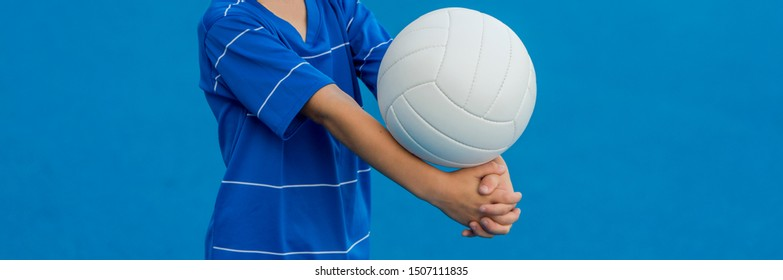 Boy playing volleyball isolated in blue.