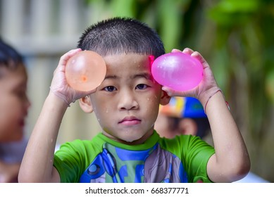 Boy playing water balloons in pool and look at this by his eyes in many color water balloons.