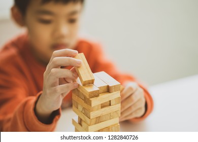 Boy playing wood tower game on wooden table. The high wooden tower of blocks falls