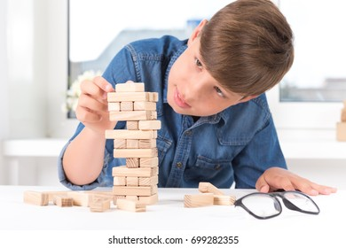 boy playing wood tower game on white table