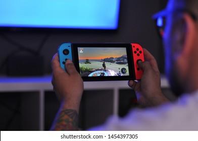 Boy playing Zelda on Nintendo Switch with blue light background