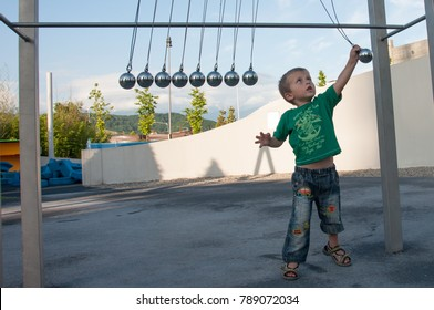 the boy plays in the big pendulum of Newton