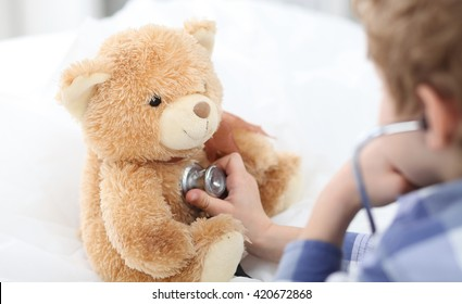 Boy plays in doctor  with stethoscope and Teddy Bear.