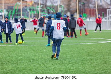 boy plays football with his team on the stadium at winter.