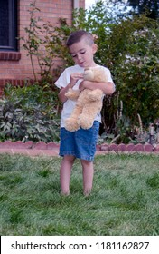 A boy plays with his favorite stuffed friend, his bear