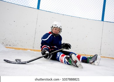 The boy plays hockey on a street skating rink.A boy on the street playing hockey.