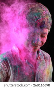 A boy plays Holi with colored powder exploding around his face in a dark background.