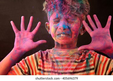 A boy plays Holi with colored powder exploding around his face in a dark background.Concept for Indian festival Holi