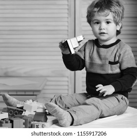 Boy plays with lego on wooden wall background. Nursery game and childhood concept. Toddler with curious face makes constructions out of bricks. Kid builds of colorful plastic blocks.