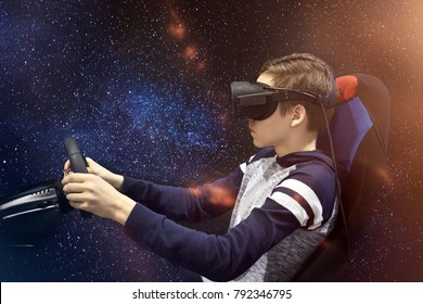 The boy plays on the simulator of games in glasses of a virtual reality against a background of the starry sky.
