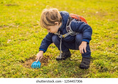 The boy plays recycling. He buries plastic disposable dishes and biodegradable dishes. After a few months, he dug up the dishes and saw that the biodegradable dishes began to decompose and plastic did