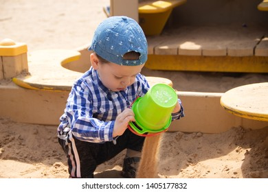 The boy plays in the sand in the sandbox. Children's games. Sandbox. Children's sand tins. Happy boy .