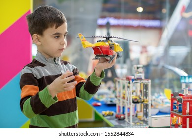 a boy plays with a toy helicopter in kindergarten
