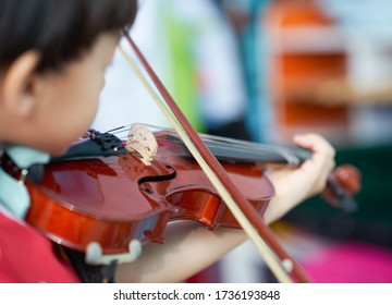 boy plays violin with bow string with copy space on blur background,selective focus