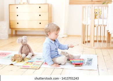 The boy plays xylophone at home. Cute smiling positive boy playing with a toy musical instrument xylophone in the children's white room. Close-up of kid playing on xylophone. Child development concept