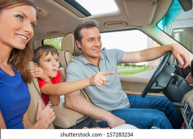 Boy is pointing his finger on something while sitting a car with his family