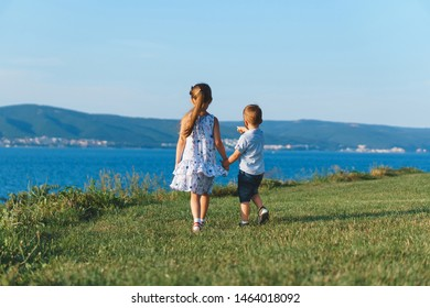 boy pointing at houses far away and holding sister's hand