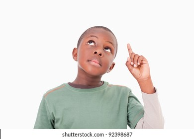 Boy pointing at something above him against a white background