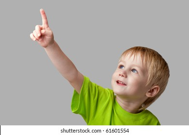 The boy points his finger upward. Half-length portrait, arms down. Gray  background