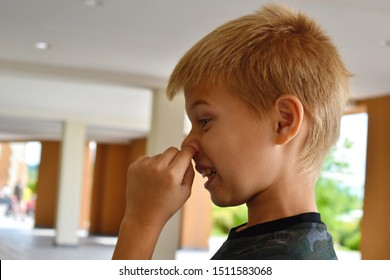 Boy pokes his nose with his finger. The child pulls out the boogers. Bad manners with bad manners. Misconduct.