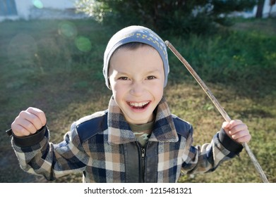 Boy portrait outdoor smiling grasping. happy smiling child outdoor playing warrior with stick