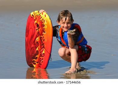 Boy posing with his body board