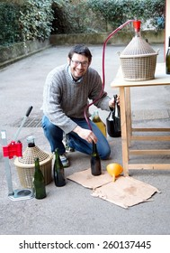 Boy pour red wine from the demijohn to glass bottles