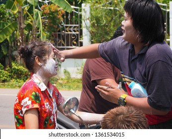 Boy powder girl on motercycle in Songkran festival in Thailand on April 13, 2018. Many boy and girl playing water at the street in their local.
