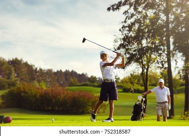 Boy practice golf with his father or trainer at golf course on warm autumn day