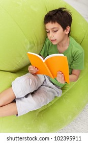 Boy practice reading relaxing on inflatable armchair