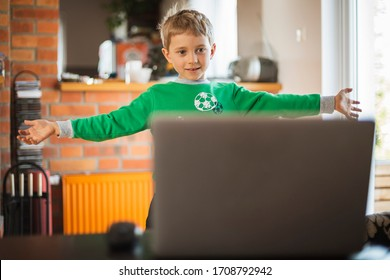The boy practices at home in front of the computer as part of an online physical education lesson due to closed schools becouse of pandemic Coronavirus Covid-19