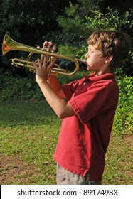 boy practicing trumpet outdoors
