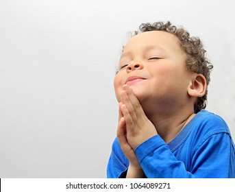 boy praying to God with hands held together with closed eyes stock photo