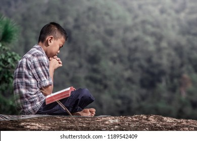 boy praying on the scriptures Bible.