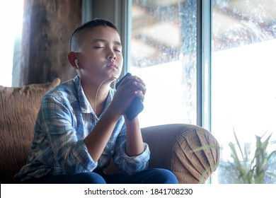 Boy praying on sofa and holding phone in hand, Listening to the voice of God, religion concept.