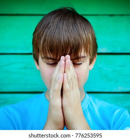 Boy praying on the Wooden Wall Background closeup