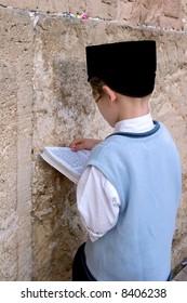 Boy praying at the wailing wall.