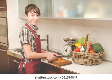 boy prepares vegetables in the kitchen - vegetarian healthy people