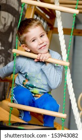 The boy of preschool age makes exercises on a gym wall bars happy smiling & looking at camera