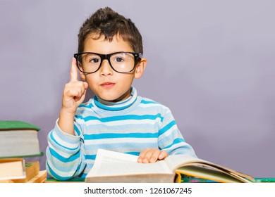 boy preschooler with glasses for books on the desktop