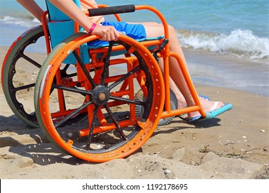 boy with problems of movement on a special wheels chair observes the sea from the beach