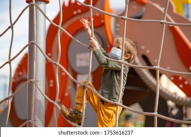 boy in a protective medical mask plays on the Playground. A child climbs up a rope ladder. Coronavirus, virus and illness protection concept. New normal concept