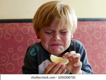 Boy puckering up after tasting a lemon